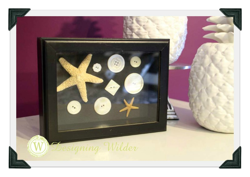 Buttons and starfish in shadow box frame.