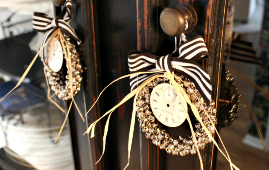 Vintage watch faces tied with raffia to adorn a farmhouse cabinet.