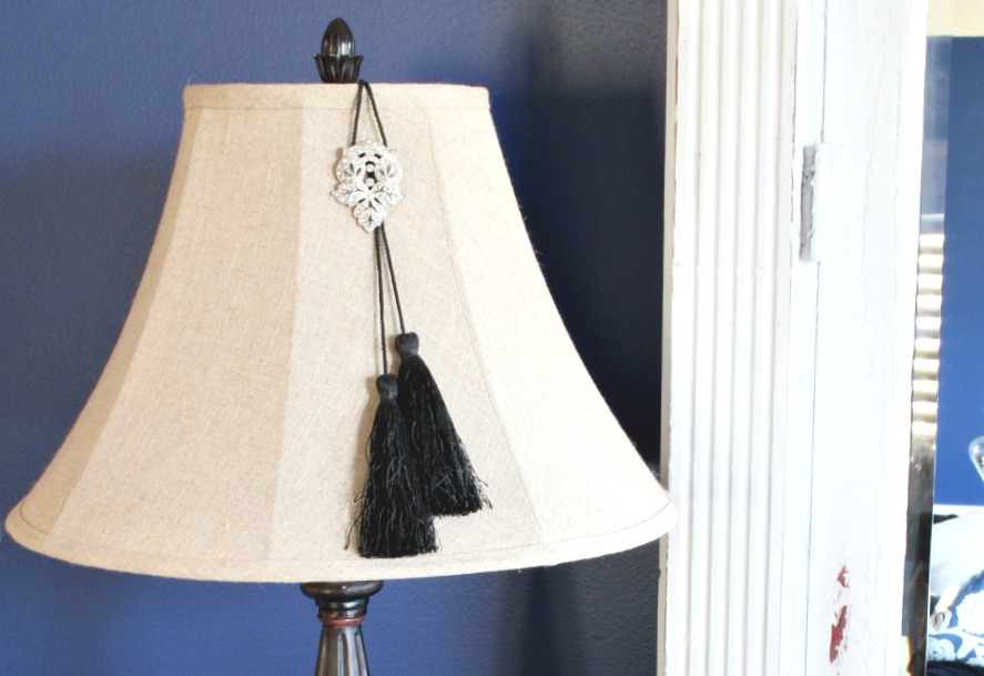 Vintage sweater clip combines with a drapery tassel adds a bit of glamour to a simple lampshade.