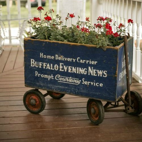 Flea market vintage crate supported by old wagon wheels make it easy to move your planter from one spot to another!