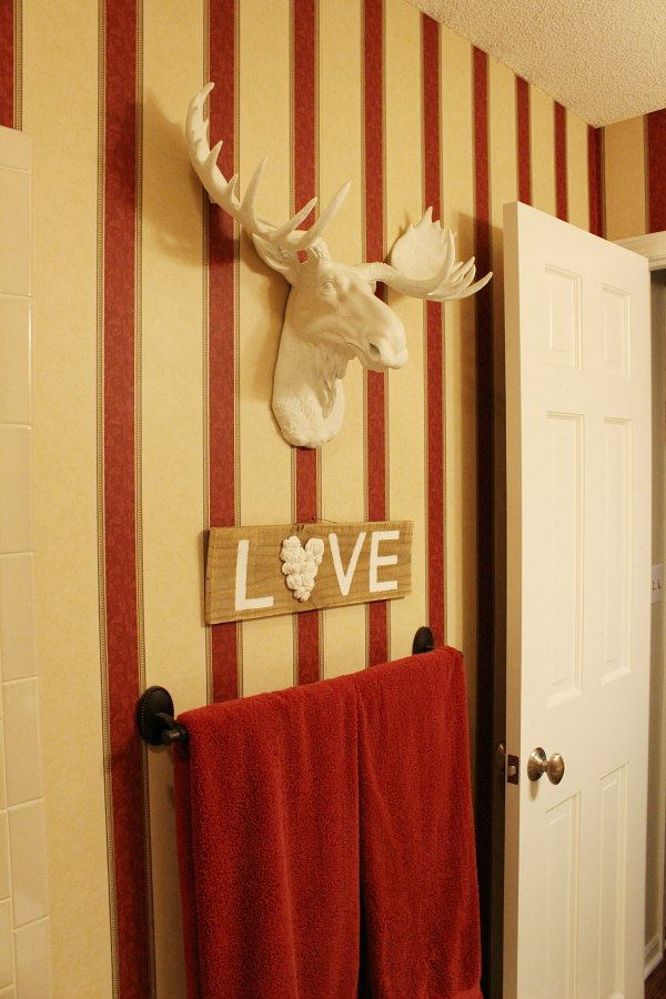 "Moose and ""love"" sign cover up tears in wallpaper."