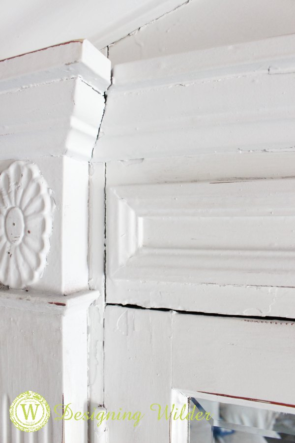 Close up of wood moldings and detail on old church window that became an entry mirror.